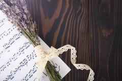 Notas da música da alfazema e do papel no fundo de madeira velho no estilo do vintage Imagens de Stock Royalty Free