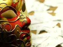 Notas da música na máscara dourada e vermelha do carnaval e no mus de papel rasgado imagem de stock royalty free