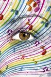 Notas da música pintadas na cara fêmea Imagem de Stock