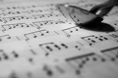 Notas da música que refletem de uma colher fotografia de stock