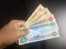 Notas da moeda do dirham de PPaying Emiratos Árabes Unidos fotografia de stock royalty free