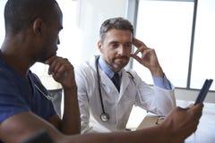 Notas da reunião e da revisão do pessoal hospitalar na tabuleta de Digitas fotografia de stock royalty free