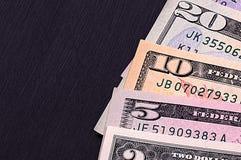 Notas de dólar abstratas de denominações diferentes no fundo preto Imagens de Stock Royalty Free