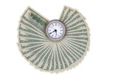 Notas de dólar americanas ventiladas para fora em torno de um relógio Fotos de Stock Royalty Free