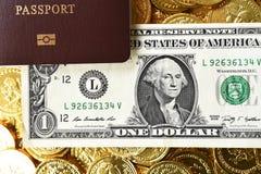 Notas de dólar com as moedas do passaporte e de ouro Fotografia de Stock Royalty Free
