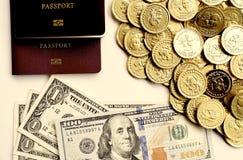 Notas de dólar com as moedas do passaporte e de ouro Fotografia de Stock