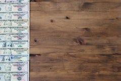 Notas de dólar dos E.U. na fileira no fundo de madeira Imagens de Stock