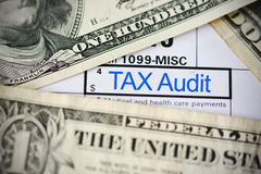 Notas de dólar dos E.U. no formulário de imposto que sugere o pagamento ou a auditoria de imposto Fotografia de Stock