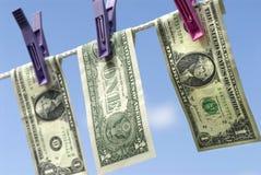 Notas de dólar dos E.U. um que penduram na linha de lavagem corda, conceito da lavagem de dinheiro Fotografia de Stock