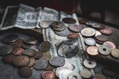 Notas de dólar e moedas dispersadas ao redor na terra com a caixa concreta e de madeira como o contexto imagem de stock