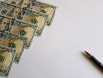 100 notas de dólar e uma pena no fundo branco Foto de Stock Royalty Free