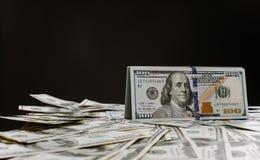 100 notas de dólar em um fundo preto Muito dinheiro, sobrepôs cédulas Imagem de Stock