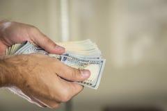 100 notas de dólar em uma mão do ` s do homem Imagens de Stock Royalty Free