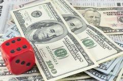 Notas de dólar empilhadas e um cubo vermelho grande Fotografia de Stock Royalty Free