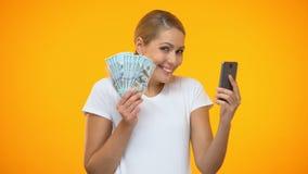 Notas de dólar guardando fêmeas novas alegres usando a aplicação do smartphone, operação bancária vídeos de arquivo