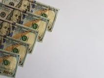 100 notas de dólar no lado esquerdo e no fundo branco Imagens de Stock