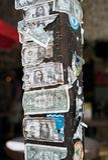 Notas de dólar rasgadas e danificadas grampeadas a um cargo de madeira foto de stock