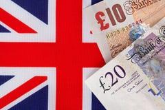 Notas de la libra sobre una bandera de Union Jack Foto de archivo libre de regalías