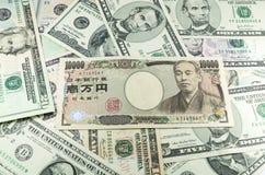 Notas de los yenes japoneses sobre fondo de muchos dólares Fotografía de archivo
