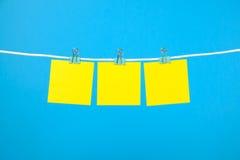 Notas de papel amarelas vazias na corda Foto de Stock Royalty Free