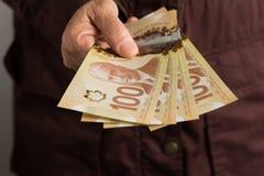 Notas de papel de Canadá Dólar Vista delantera de la mano del ` s de la mujer mayor que maneja cuentas imagen de archivo libre de regalías