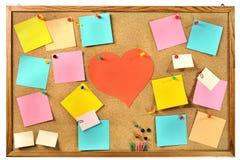 Notas de papel coloridas en blanco, materiales de oficina y corazón de papel rojo en tablero de mensajes del corcho. Foto de archivo