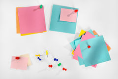 Notas de papel coloridas vazias múltiplas e pinos coloridos no fundo branco. Fotografia de Stock Royalty Free