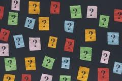 Notas de papel con los signos de interrogación en la pizarra imagen de archivo libre de regalías