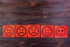 Notas de papel vermelhas com feliz, alegria, raiva, riso e as caras tristes no quadro-negro vignette imagens de stock royalty free