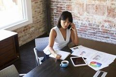 Notas de On Phone Making da mulher de negócios no original na sala de reuniões fotografia de stock
