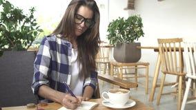 Notas de trabalho da escrita do estudante fêmea no café local do lugar frequentado do estudo video estoque