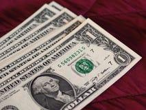 Notas de um dólar, Estados Unidos sobre o fundo vermelho de veludo fotografia de stock royalty free