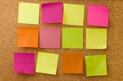 Notas del color sobre corkboard Imagenes de archivo