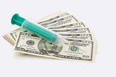 Notas do dólar americano, seringa colocada na parte superior, fim acima Fotografia de Stock