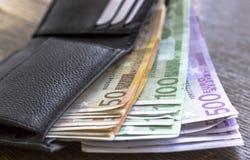 Notas do dinheiro do Euro na carteira no fundo de madeira Fotografia de Stock