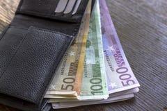Notas do dinheiro do Euro na carteira no fundo de madeira Foto de Stock