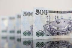Notas do saudita refletidas em um vidro escuro Foto de Stock Royalty Free