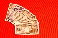 Notas dos ienes japoneses no vermelho Imagens de Stock Royalty Free