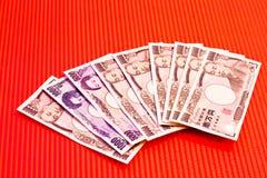 Notas dos ienes japoneses no vermelho Imagens de Stock