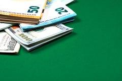 Notas e notas de dólar do Euro no fundo verde imagens de stock royalty free