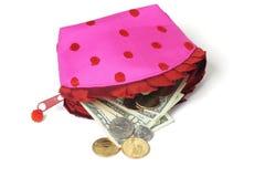 Notas e moedas dos E.U. que derramam para fora da bolsa cor-de-rosa imagem de stock royalty free