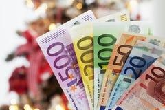 Notas euro avivadas cerca encima del árbol de navidad en fondo Fotografía de archivo libre de regalías