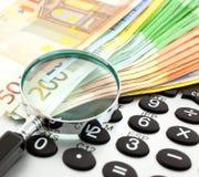 Notas euro con la calculadora y la lupa Imagen de archivo libre de regalías