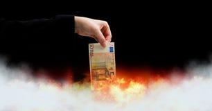 Notas euro del dinero que queman en fuego foto de archivo