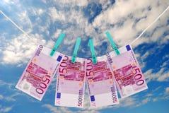 Notas euro del dinero que se secan en la cuerda para tender la ropa Fotos de archivo