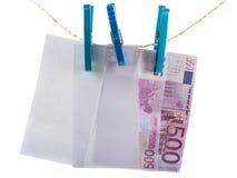 Notas euro que lavan planchan en cuerda para tender la ropa Foto de archivo