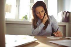 Notas fêmeas novas da escrita ao falar no telefone Foto de Stock Royalty Free