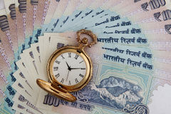 Notas indianas da rupia da moeda com relógio antigo Foto de Stock