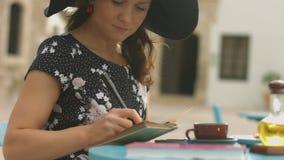 Notas inspiradas de la escritura de la señora joven en la libreta, disfrutando de la afición en café de la calle metrajes