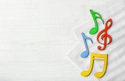 Notas musicais coloridas que encontram-se em folhas de música fotos de stock